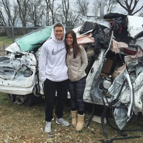 The couple in front of the vehicle's twisted remains.