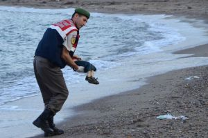 Alan Kurdi's body being carried away from the shore.
