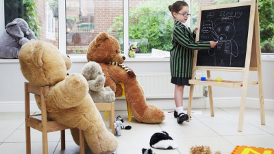 Young girl pretending to teach her teddy bears