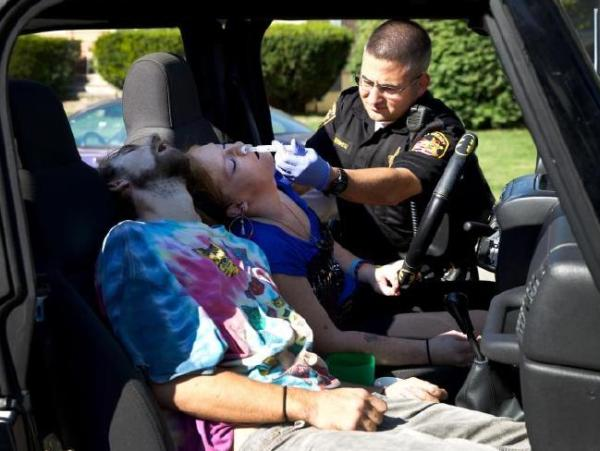 An officer administers the drug Narcan to counteract the Fentanyl
