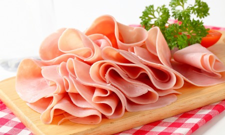 Thinly sliced ham on a chopping board