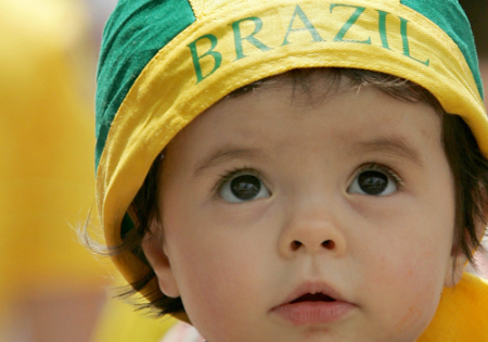 A young Brazil soccer fan watches a screen in the centre of Cologne ahead of World Cup soccer match against Sweden