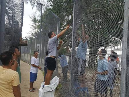refugees fixing fence
